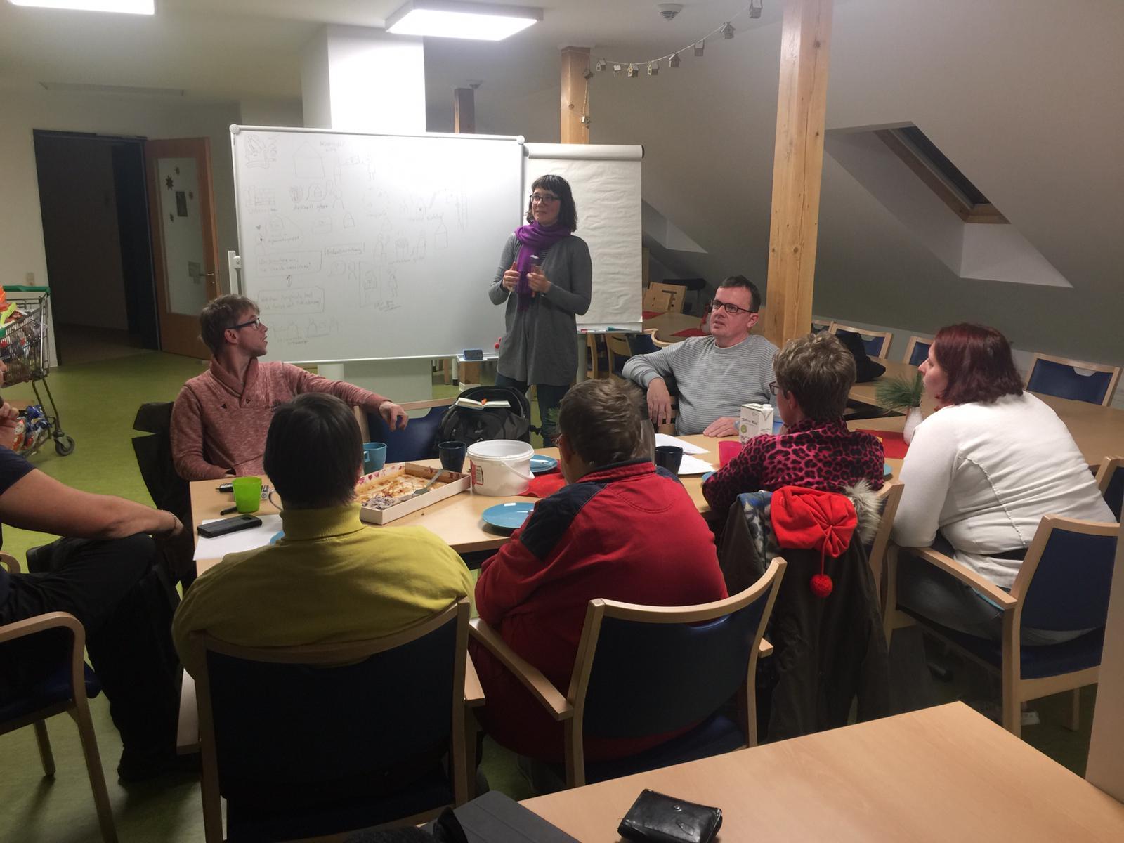 Seminarraum. Gruppe sitzt an länglichem Tisch. ich dahinter, neben mir eine Pinnwand. Ich rede gerade vor der Gruppe.