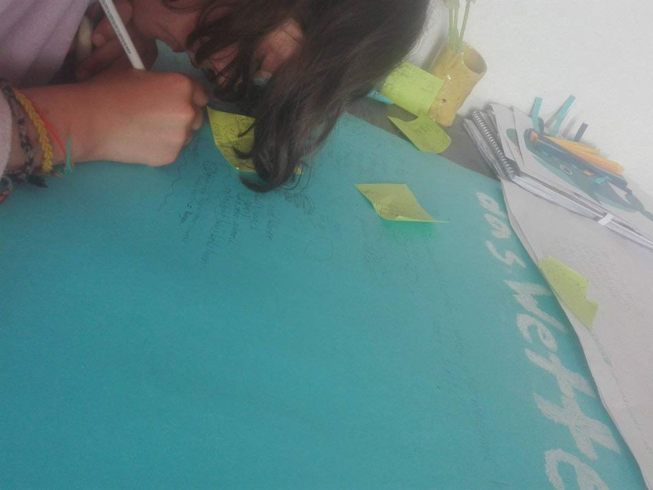 Antonia am Tisch über das blaue Plakat gebeugt konturiert am Schreiben