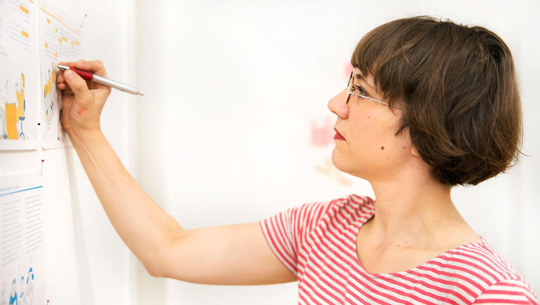 ich zeichne konzentriert etwas auf ein an die Wand befestigtes Papier